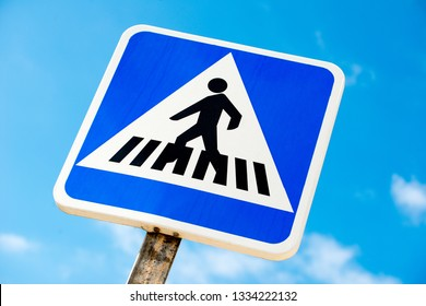 Low angle view of Spanish pedestrian crossing road sign, against a background of blue sky with small clouds.