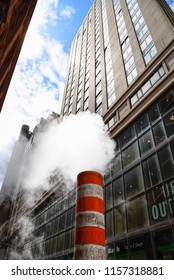 Low angle view of steam coming out stack for venting the district heating system in downtown of New York