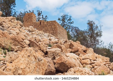 low angle view of the stone mamluk era flour mill at ein gedi spring in israel with a rocky hillside in the foreground and cloudy sky in the background