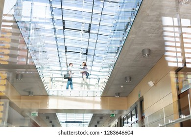Low angle view of students walking on glass floor at university campus