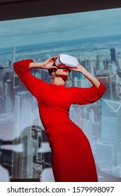 low angle view of stylish woman in red dress and virtual reality headset on city background
