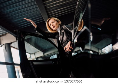 low angle view of surprised blonde girl near black car with open door