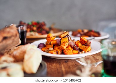 Low angle view of table served with traditional British Sunday roast dinner, featuring roasted chicken, squash and sweet potatoes