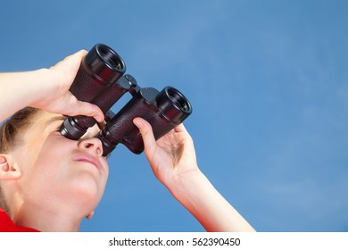 Low angle view of teen boy wearing red tshirt looking through binoculars against blue summer sky