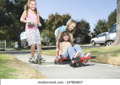 Low angle view of three children playing with skateboard and scooter