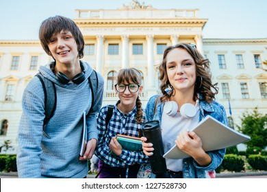 Low angle view of three defferent age students on university campus in autumn time.