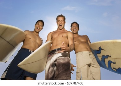 Low angle view of three happy multiethnic friends with surfboards