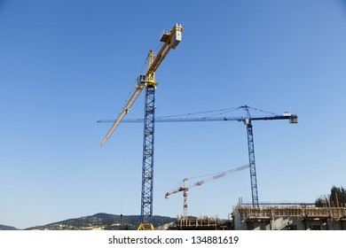 Low angle view of three tower cranes in a rural construction site, on a clear day.