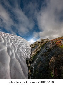 Low angle view through gorge of ice and rocks towards the sky and aligned sunstar, Sognefjell, Norway