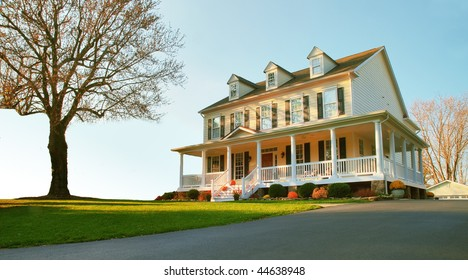 Low angle view of a traditional upscale home with a single tree in the front yard. Horizontal format.