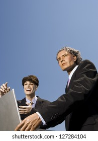 Low angle view of two mannequins portraying businessmen using a laptop
