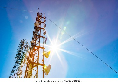A low angle view of two mobile communication data transmitter and GPS signal towers, against a blue sky with bright sun shine and colorful lens flare