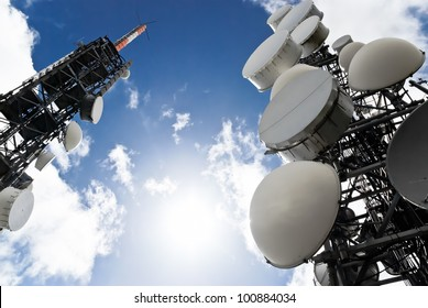 low angle view of two telecommunications towers against the sky