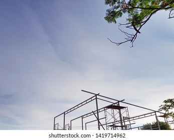 Low Angle View of Unfinished Warehouse Construction Against Blue Sky