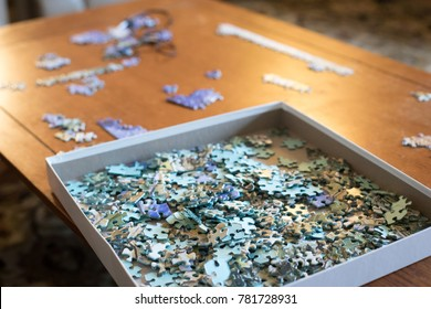 Low angle view of an unsolved puzzle, with pieces piled in a square box made of cardboard, on a wood coffee table