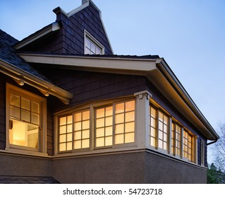 Low angle view of the upper floors of a large house. The windows are illuminated with interior lighting. Square shot.
