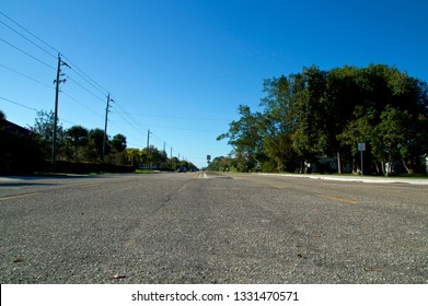A low angle view of Vanderbilt Drive road in Bonita Springs Florida, with cars and bicycles in the distance and a clear blue sky.