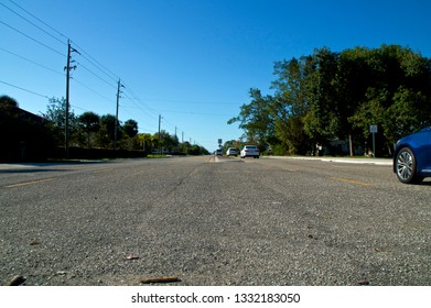 A low angle view of Vanderbilt Drive road in Bonita Springs Florida, with car traffic and a clear blue sky.