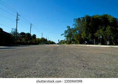 A low angle view of Vanderbilt Drive road in Bonita Springs Florida, with a cyclist and cars in the distance and a clear blue sky.