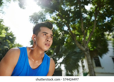 Low angle view of Vietnamese sportsman in headphones taking break after energy-sapping training in sunny park