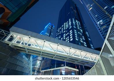Low angle view of walkway bridge and skyscraper office building , night scene