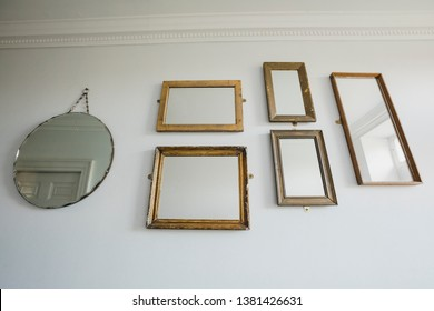 Low angle view of a wall in a house which has a variety of different shaped mirrors hanging on the wall.