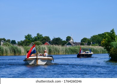 Low angle view from the water towards two recreational motor boats cruising along one of the canals lined with reeds beds between Frisian lakes in the Netherlands with a clear blue sky;