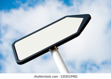 Low angle view of a white, blank, pointing the way, information sign post against a blue sky with clouds.