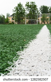 Low angle view at white line of an artificially turfed football field with goal on background