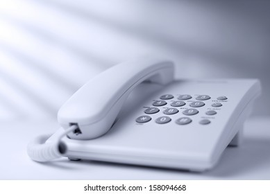 Low angle view of a white office dial up landline or terrestrial telephone with handset and keypad for telephonic communication