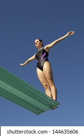 Low angle view of a woman about to dive backwards off a diving board against clear blue sky