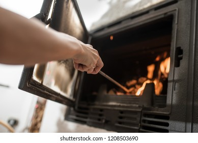 Low angle view of a woman arranging ashes and logs with iron poker in a burning fire in fireplace.