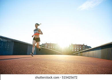 Low angle view of woman running down concrete and iron railing bridge with bright sunlight reaching over urban theme background