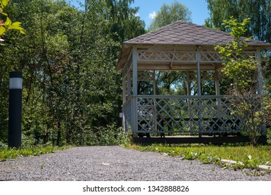Low angle view of wooden summerhouse standing among lush green trees on bright sunny summer day