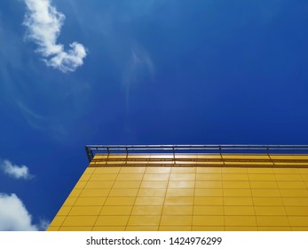 Low Angle View of Yellow Tiled Building Exterior Against Blue Cloudy Sky