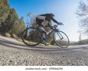 Low angle view of a young adult man riding a racing bike downhill.