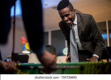 Low angle view of young African American office worker playing table football with colleague and smiling joyfully