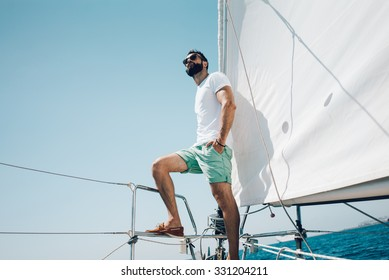 Low angle view of young bearded man standing on the yacht