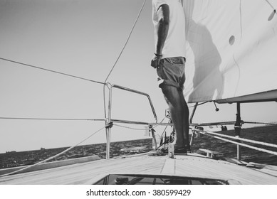 Low angle view of young bearded man standing on the yacht in sunny day. Horizontal black and white mockup