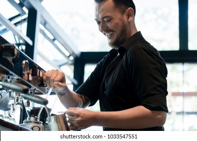 Low angle view of a young cheerful barista wearing black shirt while preparing coffee at an automatic machine in a modern coffee shop