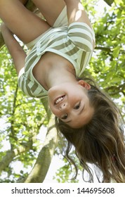 Low angle view of a young girl hanging upside down from tree