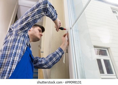 Low Angle View Of A Young Male Handyman Fixing Window