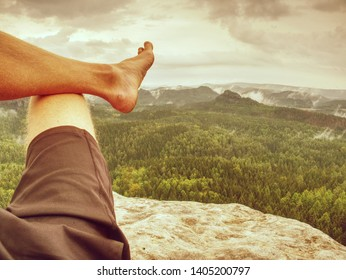 Low angle view of young man sit down on mountain edge barefoot. Male hiker sit barefoot on rock with rain forest in background.