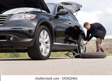 Low angle view of a young man with a roadside puncture changing the tyre on his car for his spare on a country road