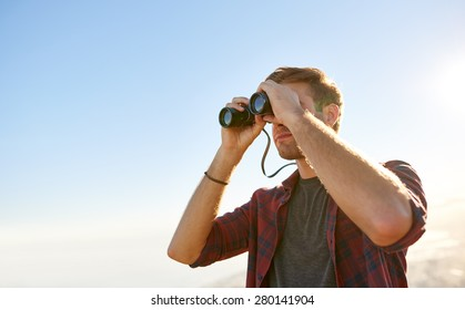 Low angle view of a young man looking through binoculars while outdoors in nature