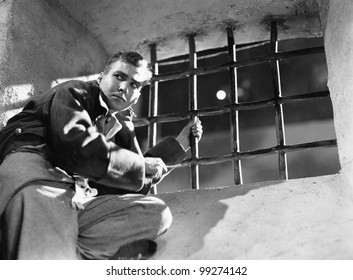 Low angle view of a young man trying to escape from a prison cell