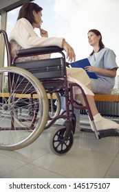 Low angle view of a young nurse talking to patient in wheelchair in hospital