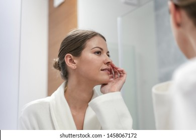 Low angle view of young and pretty woman in white bathrobe standing in bright light bathroom with mirror. She looking at her reflection, holding hand near face, checking skin