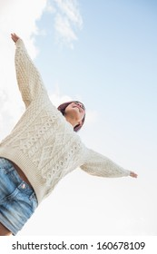 Low angle view of a young woman in white sweater and denim shorts stretching her arms against the sky