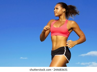 Low angle view of young woman in sportswear jogging against blue sky